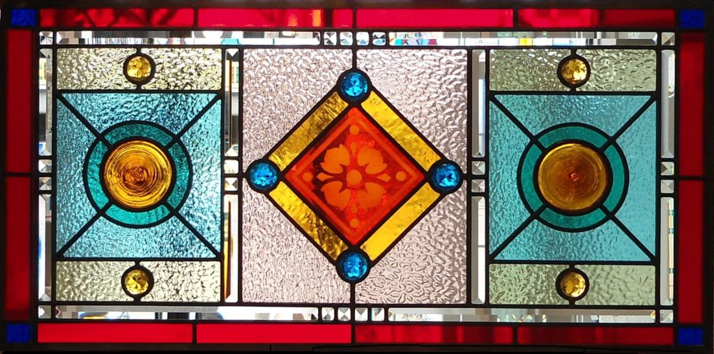Stained glass window with etched red centre by The Glass Studio