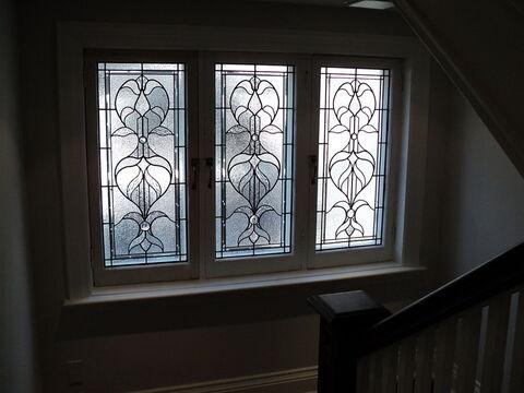 Three leaded windows on a stairway landing