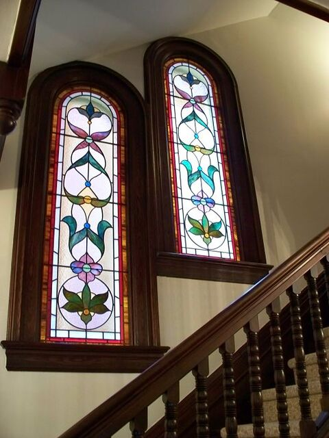 Two stained glass Victorian windows on a stairway