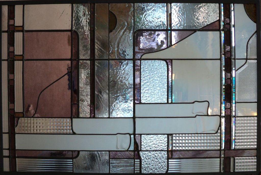 Abstract geometric stained glass with pink and white glass