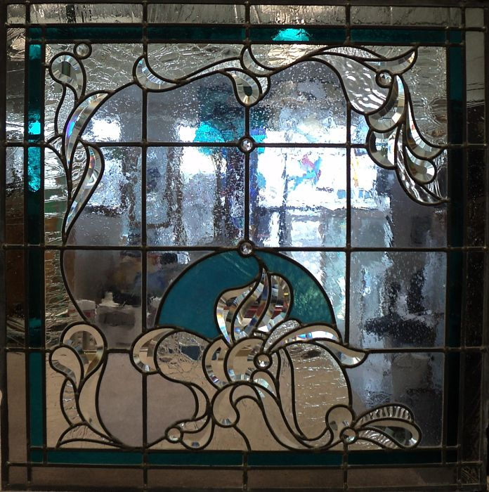 Stained glass window with blue colour accents and bevelled glass