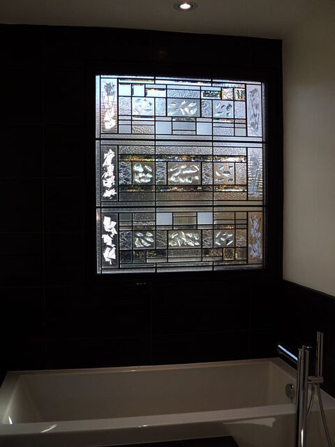 Contemporary stained glass window beside bathtub