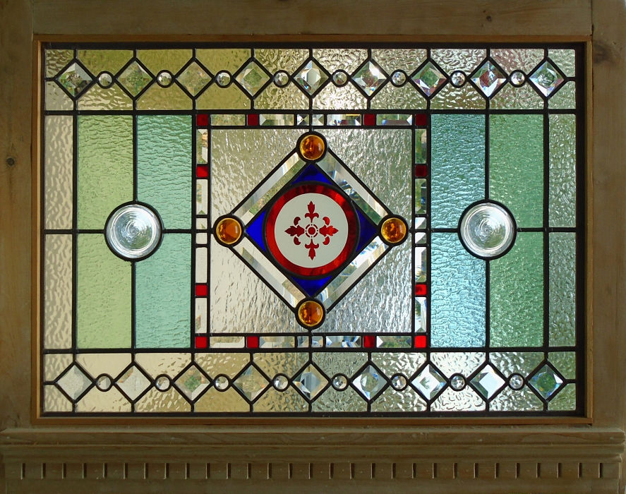 Stained glass with a red flashed round centre by The Glass Studio