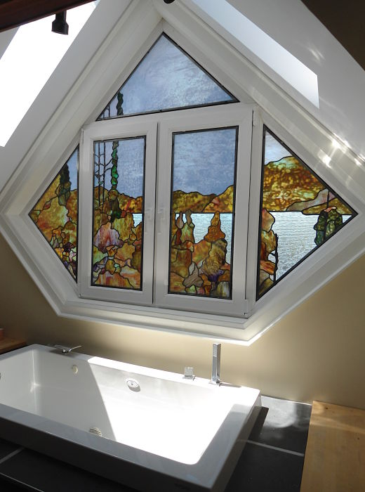 Stained glass landscape window in bathroom