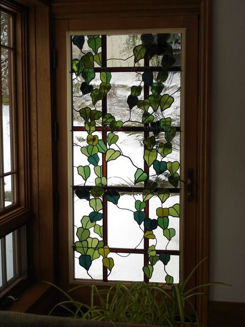 Ivy trellis themed stained glass window in a door