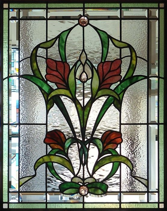 Stained glass window with pink red flowers and a bevelled border