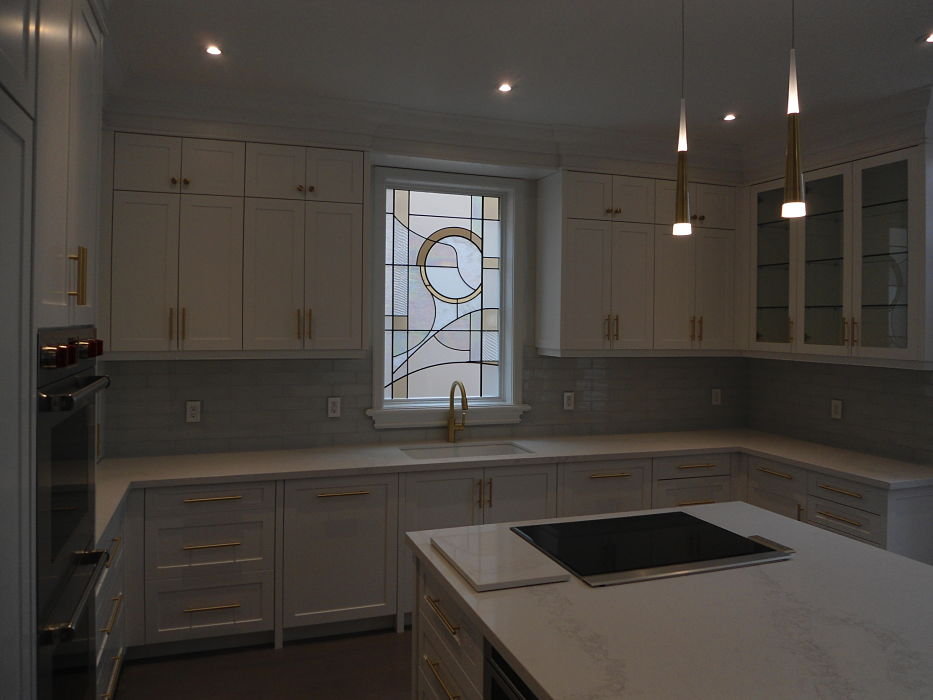 A modern white kitchen with a stained glass window