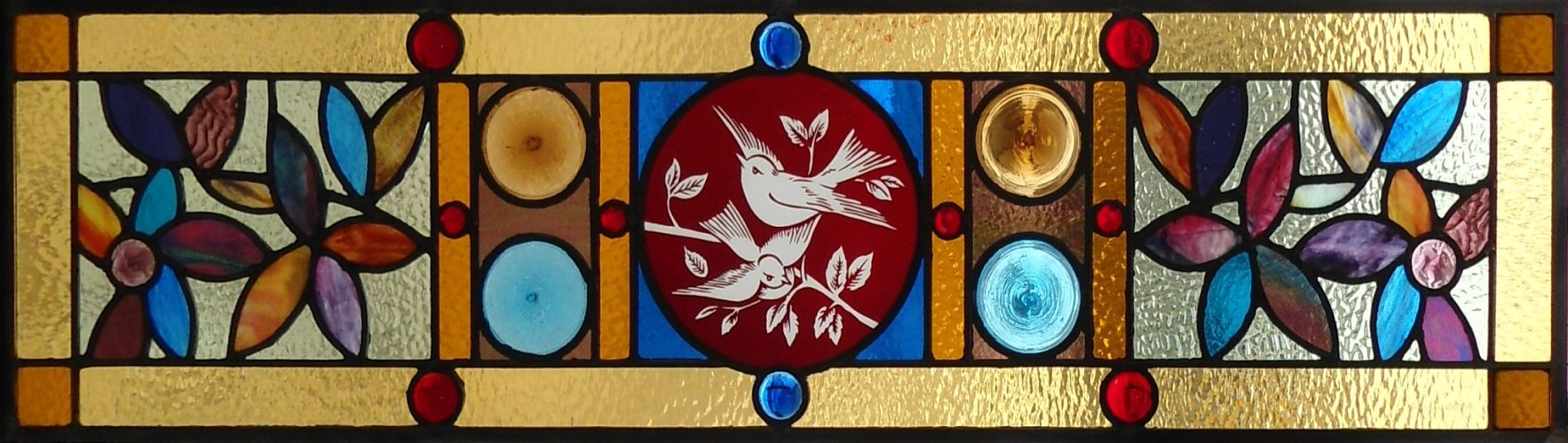 Stained glass window with red flashed glass birds centre by The Glass Studio